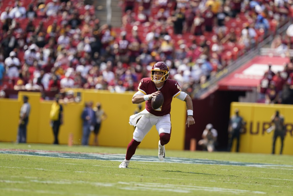 Washington Football Team quarterback Taylor Heinicke (4) running with the ball during the first half of an NFL football game against the Los Angeles C...