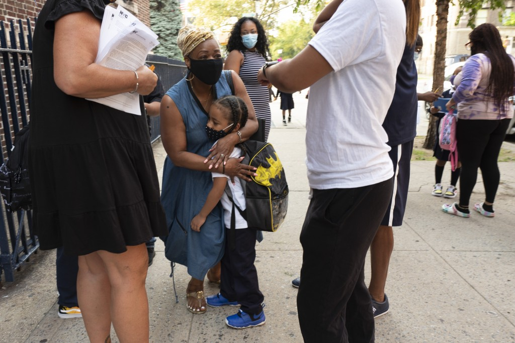 A boy gets a hug as he arrives for the first day of school at Brooklyn's PS 245, Monday, Sept. 13, 2021 in New York. Classroom doors are swinging open...