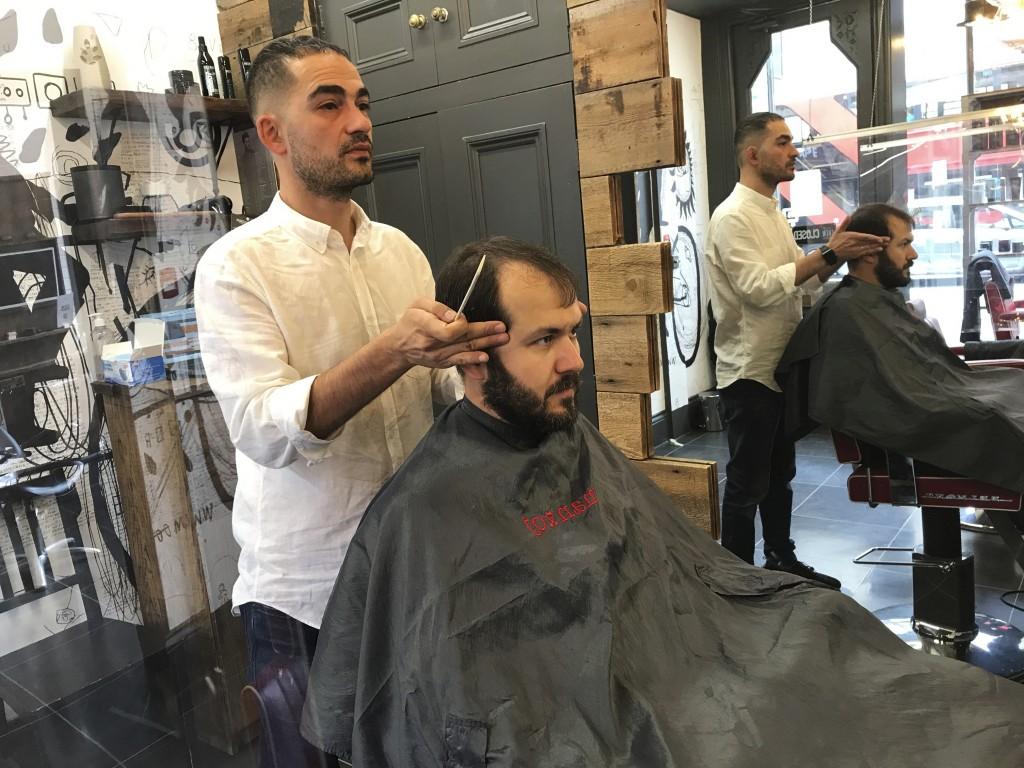 Rado Asatrian cuts a customer's hair at Man-oj hair salon in London's financial district, Thursday, Sept. 9, 2021. Before COVID-19, Asatrian usually h...