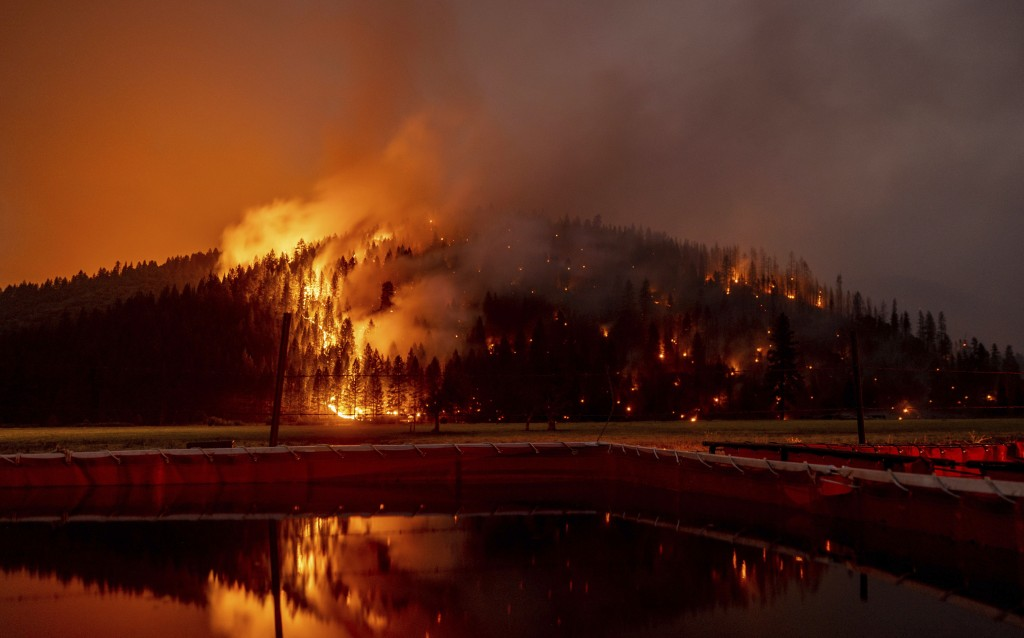 FILE - In this Aug. 21, 2021 file photo long exposure photo, flames from the Dixie Fire spread in Genesee, Calif. A Pacific Gas & Electric troubleshoo...