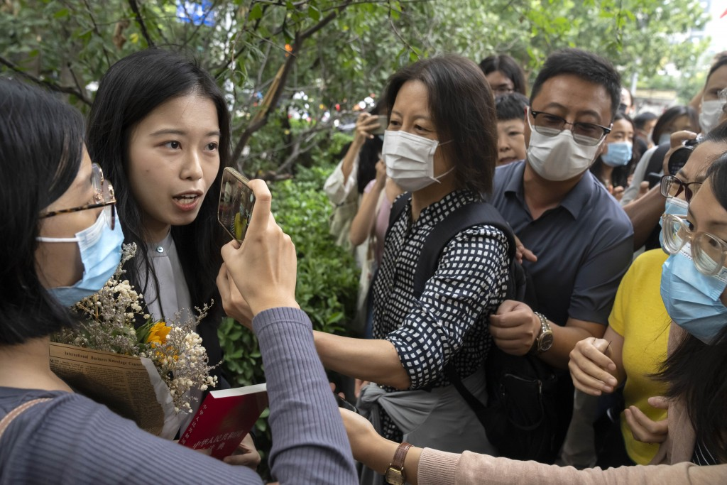 Zhou Xiaoxuan, left, a former intern at China's state broadcaster CCTV, is accosted by hostile bystanders outside a courthouse in Beijing, Tuesday, Se...