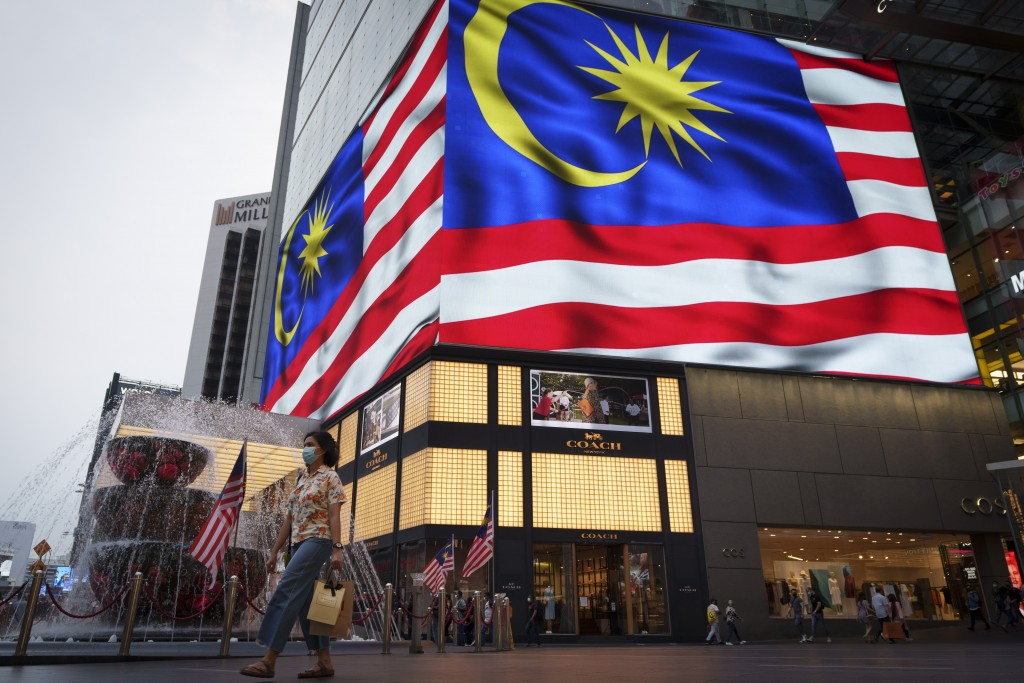 People wearing protective masks cross a street outside a shopping mall, amid the coronavirus disease (COVID-19) outbreak in Kuala Lumpur, Malaysia, Tu...