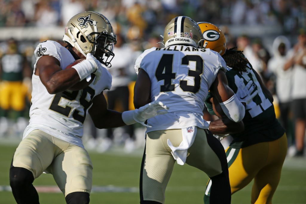 New Orleans Saints cornerback Paulson Adebo, left, intercepts a pass thrown by Green Bay Packers quarterback Aaron Rodgers during the second half of a...