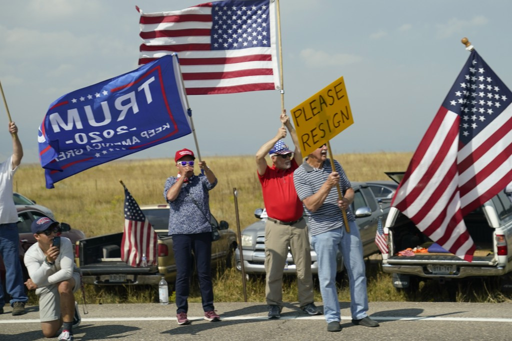 Protesters hold signs on the side of the road as seen through the window of a motorcade vehicle traveling with President Joe Biden to the Flatirons Ca...