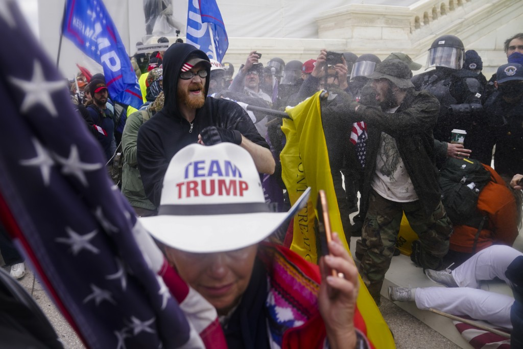 FILE - In this Jan. 6, 2021, file photo, insurrections loyal to President Donald Trump try to break through a police barrier at the Capitol in Washing...