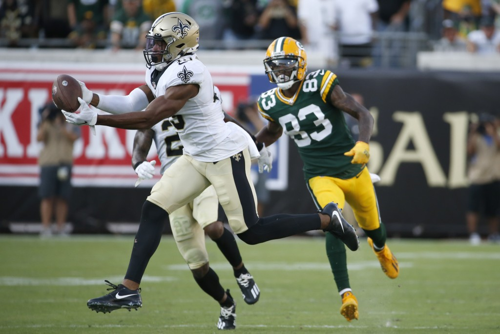 New Orleans Saints free safety Marcus Williams, left, intercepts a pass in front of Green Bay Packers wide receiver Marquez Valdes-Scantling (83) duri...
