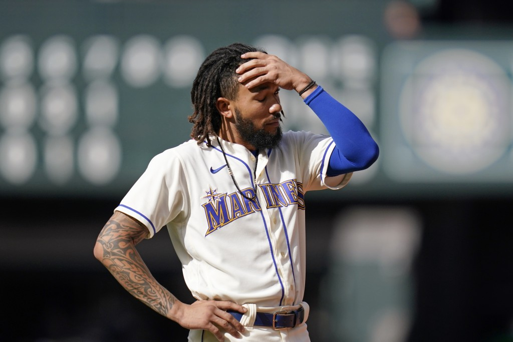 Seattle Mariners' J.P. Crawford stands on the field after he flew out to end the seventh inning of a baseball game against the Arizona Diamondbacks, S...