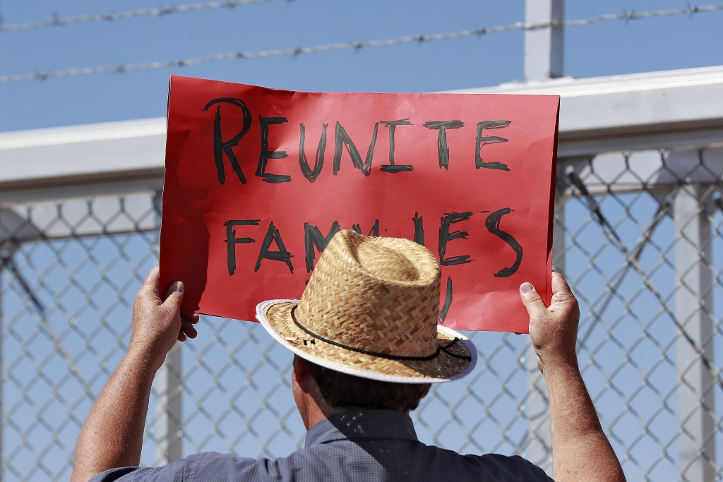 FILE - In this June 21, 2018 file photo, a protester holds a sign outside a closed gate at the Port of Entry facility in Fabens, Texas, where tent she...