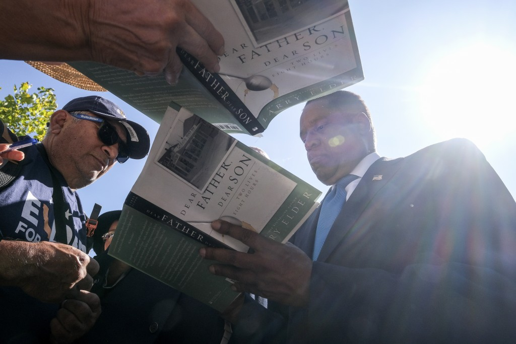 Republican conservative radio show host Larry Elder, right, signs autograph for supporters at a rally for the California gubernatorial recall election...