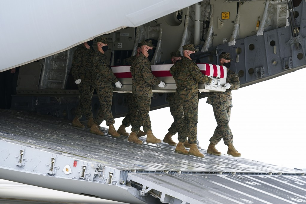 A Marine Corps carry team moves a transfer case containing the remains of Marine Corps Humberto Sanchez, 22,of Logansport, Ind., Sunday, Aug. 29, 202...