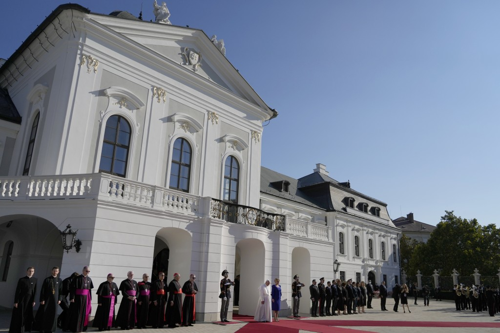 Pope Francis, white figure at center bottom, flanked by Slovakian President Zuzana Caputova, attends a welcoming ceremony at the presidential palace i...