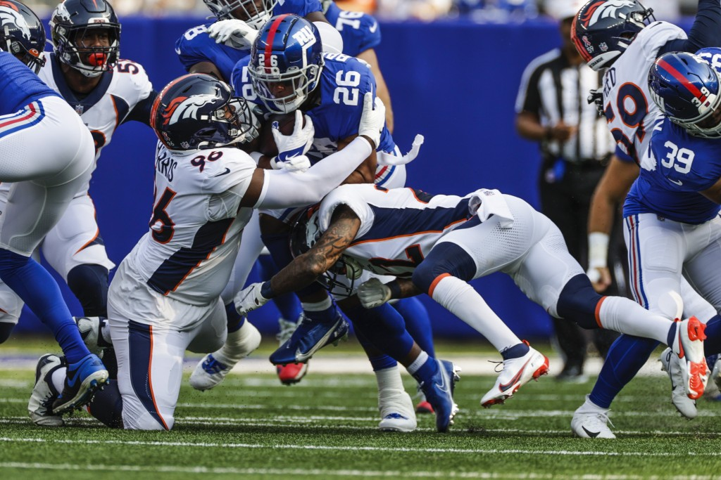 New York Giants running back Saquon Barkley (26) is tackled by Denver Broncos' Shelby Harris (96) and Kareem Jackson (22) during the first half of an ...