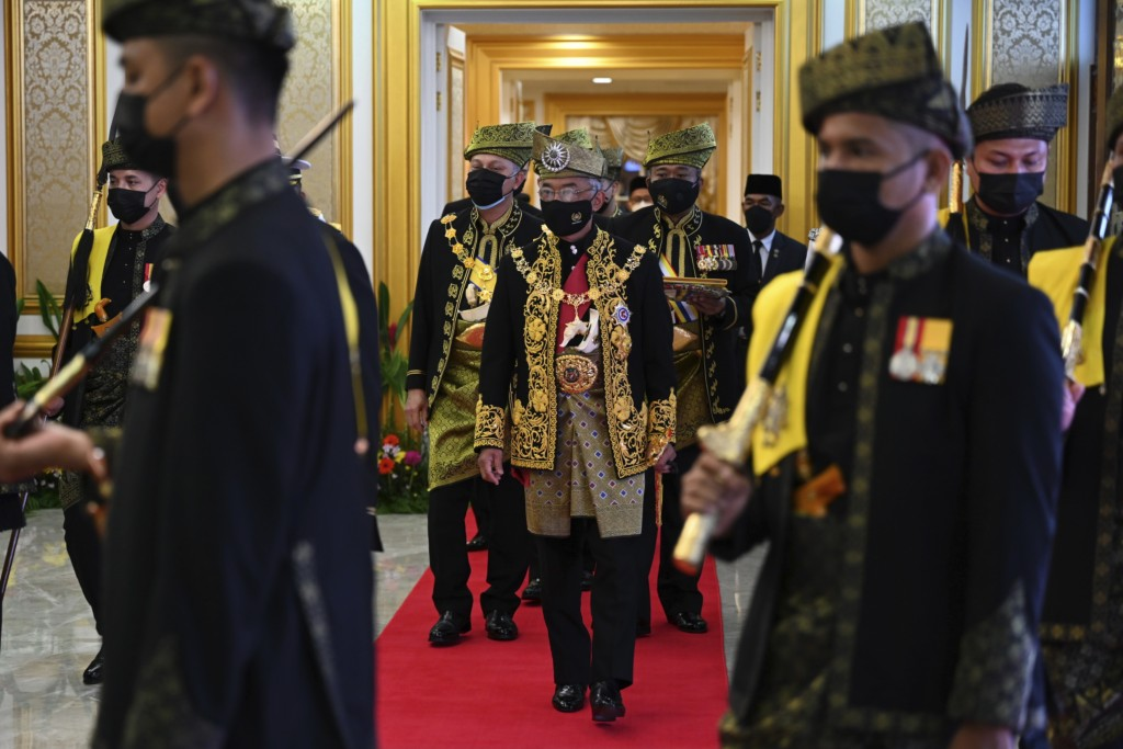 In this photo released by Malaysia's Department of Information, Malaysia's King Sultan Abdullah Sultan Ahmad Shah, center, arrives to the opening cere...
