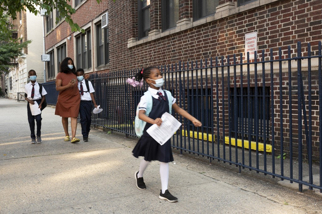 A girl leads her mother and brothers as they arrive at Brooklyn's PS 245, Monday, Sept. 13, 2021, in New York. Classroom doors are swinging open for a...