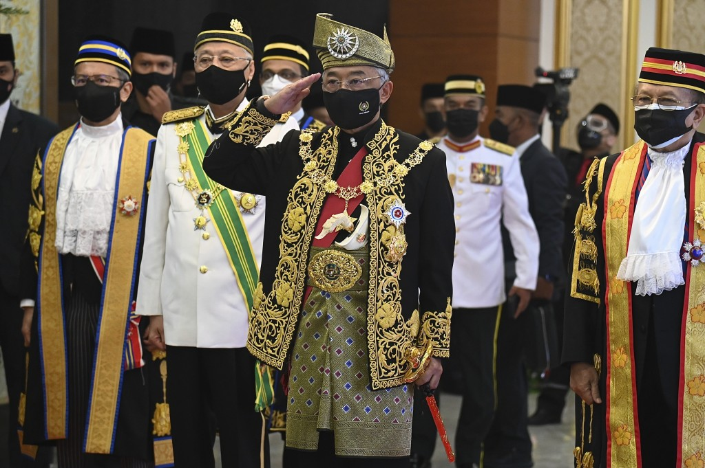 In this photo released by Malaysia's Department of Information, Malaysia's King Sultan Abdullah Sultan Ahmad Shah, center, salutes as he and Prime Min...