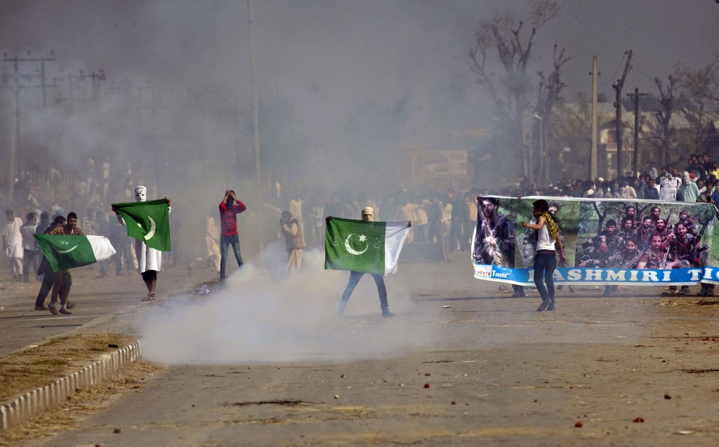 FILE - In this Sept. 25, 2015,file photo, masked Kashmiris hold a national flag of Pakistan and a banner displaying militant leaders of the Hizb-ul Mu...