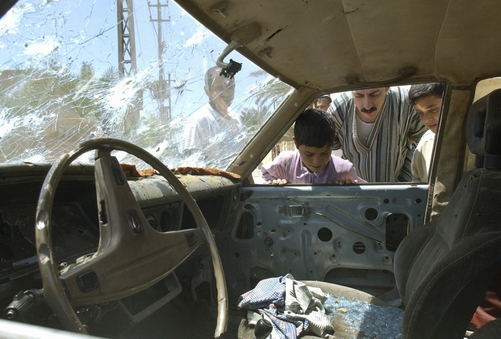FILE - In this April 29, 2003, file photo, residents of Fallujah, Iraq look into a bullet riddled car outside a school where U.S. soldiers fired on de...