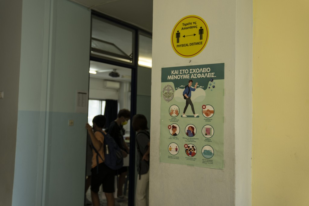 Children enter a classroom with a view of signs with health guidance on the wall in the foreground, in Athens, Monday, Sept. 13, 2021. Public and priv...