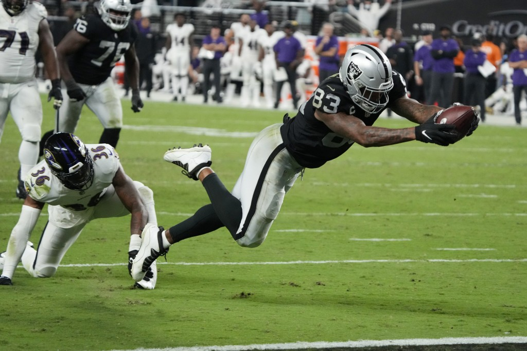 Las Vegas Raiders tight end Darren Waller (83) dives into the end zone for a touchdown against the Baltimore Ravens during the second half of an NFL f...