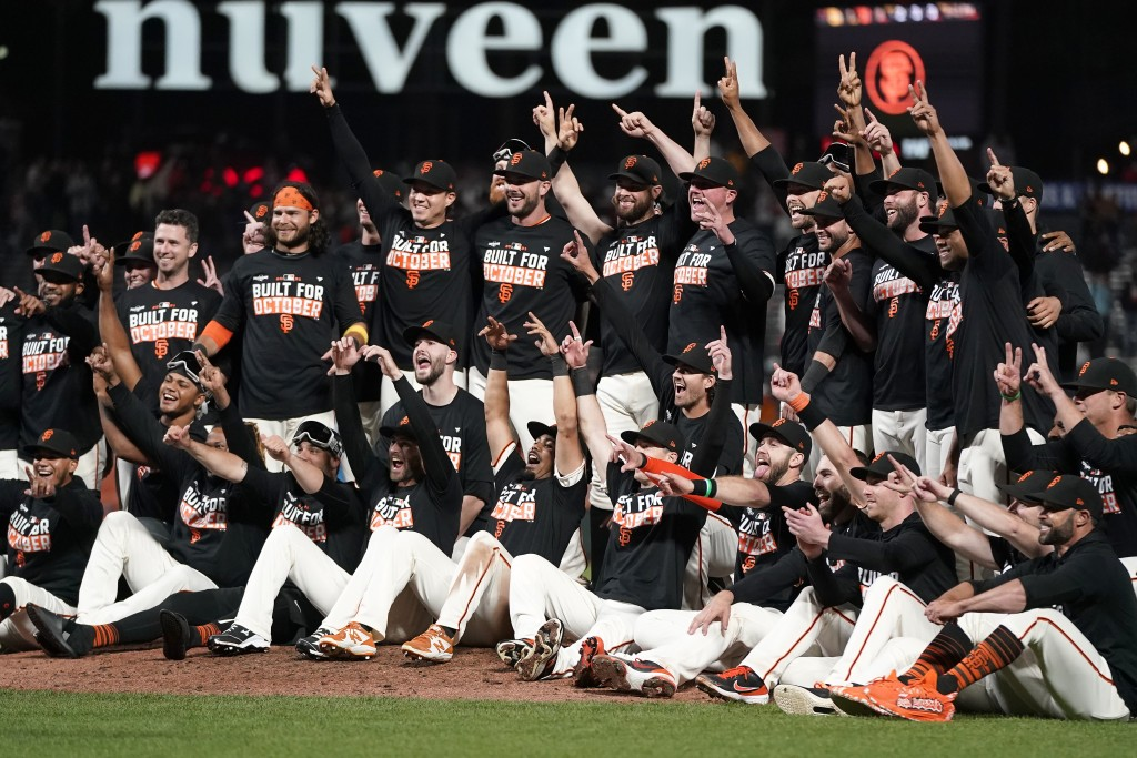 San Francisco Giants players celebrate after defeating the San Diego Padres in a baseball game to clinch a postseason berth in San Francisco, Monday, ...