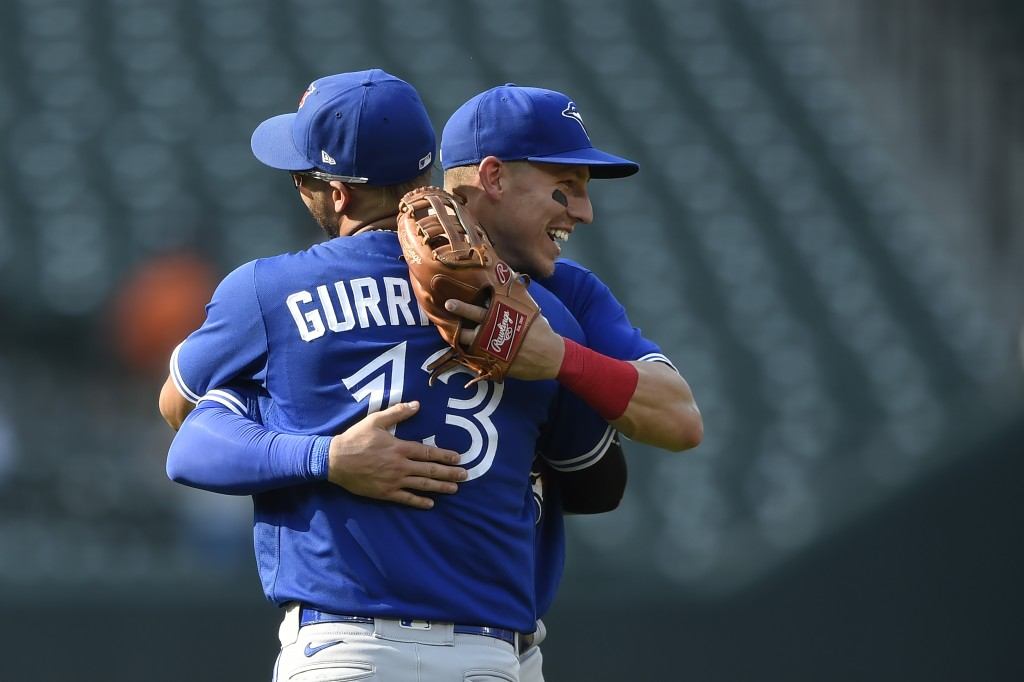 Toronto Blue Jays' Lourdes Gurriel Jr., left, and Jake Lamb celebrate their win over the Baltimore Orioles in a baseball game Sunday, Sept. 12, 2021, ...