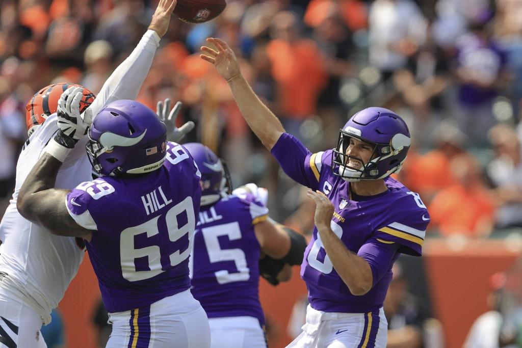 Minnesota Vikings quarterback Kirk Cousins (8) passes as Cincinnati Bengals defensive end Trey Hendrickson, left, pressures in the first half of an NF...