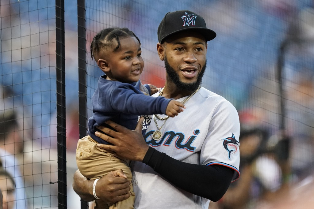 Miami Marlins' Bryan De La Cruz holds his son before a baseball game against the Washington Nationals at Nationals Park, Monday, Sept. 13, 2021, in Wa...