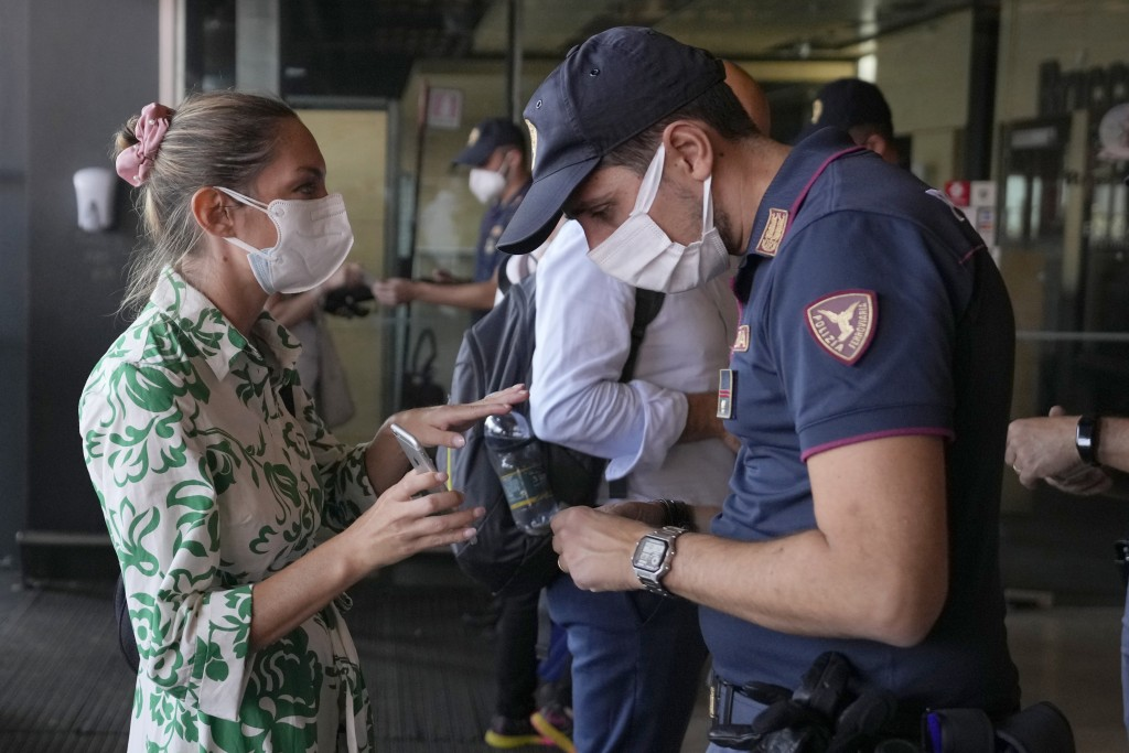 A police officer checks a passenger's phone at Porta Garibaldi train station, in Milan, Italy, Wednesday, Sept. 1, 2021. Italy's government vowed to c...