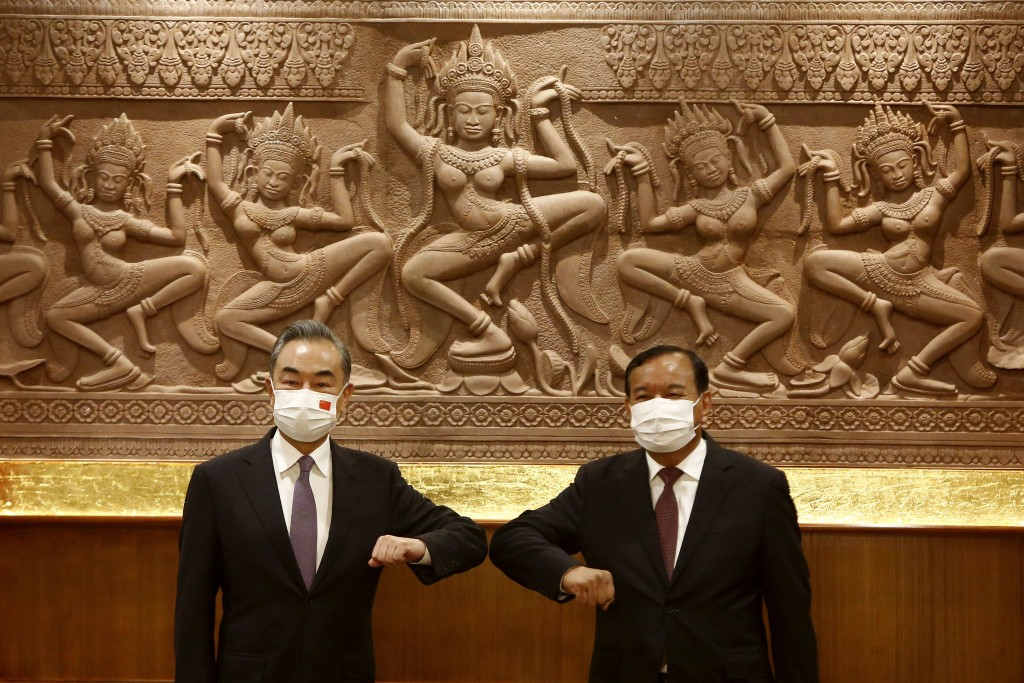 Chinese Foreign Minister Wang Yi, left, greets with Cambodian counterpart Prak Sokhonn in Phnom Penh, Cambodia, Sunday, Sept. 12, 2021. Wang is visiti...