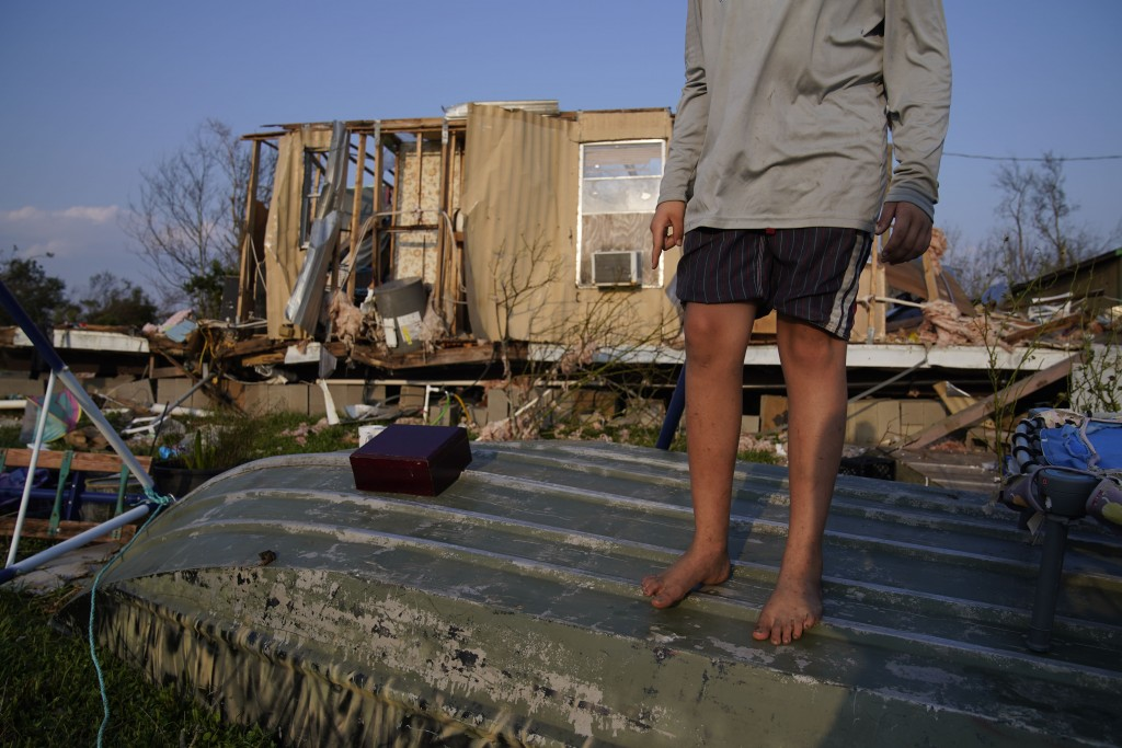 FILE - In this Sept. 4, 2021 file photo, Aiden Locobon stands on a boat near the remnants of his family's home destroyed by Hurricane Ida,  in Dulac, ...