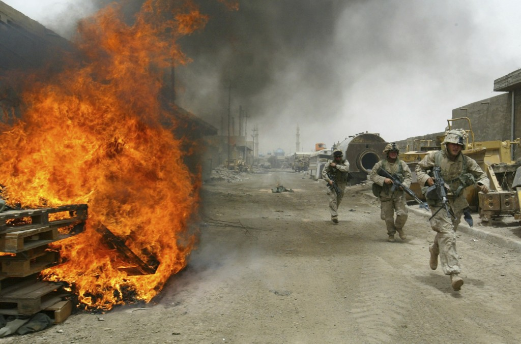 FILE - In this April 30, 2004, file photo, U.S. Marines burn their fortifications on front line positions in Fallujah, Iraq, before pulling out of the...