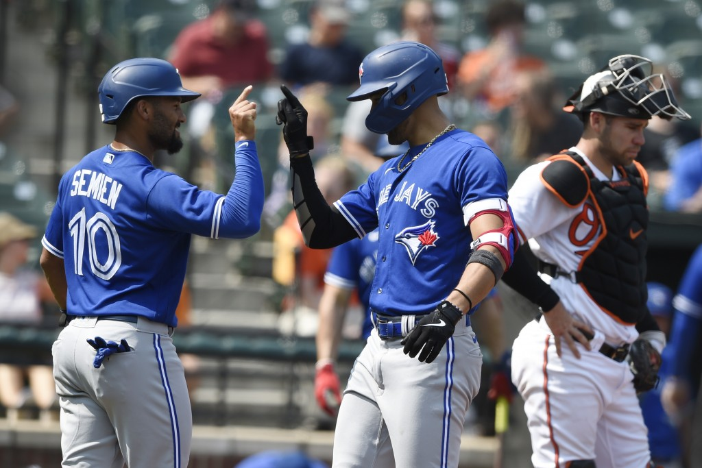 Toronto Blue Jays' Lourdes Gurriel Jr. right, is congratulated by Marcus Semien after hitting a grand slam against the Baltimore Orioles in the first ...
