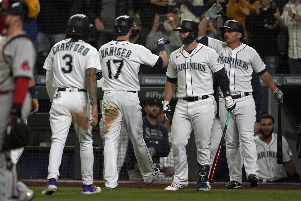 Seattle Mariners' Mitch Haniger (17) is greeted by teammates after he hit a three-run go-ahead home run against the Boston Red Sox during the seventh ...