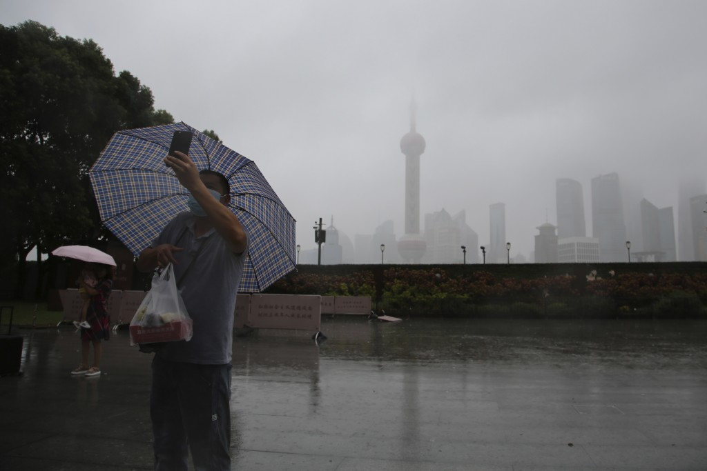 A resident wearing a mask and holding an umbrella takes a photo near the bund overlooking the skyline in Shanghai, China, Monday, Sept. 13, 2021. Flig...