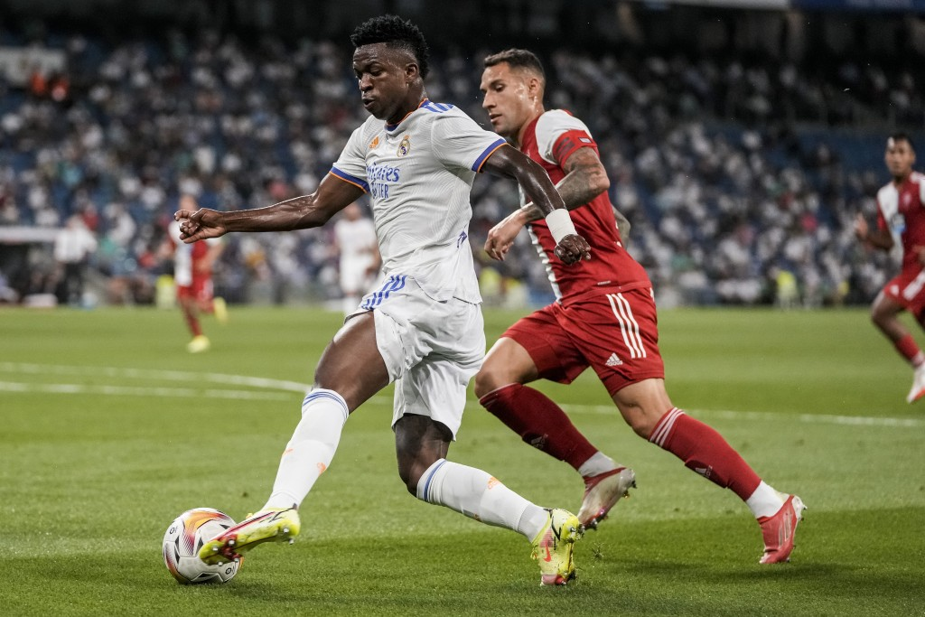 Real Madrid's Vinicius Junior, left, vies for the ball during the Spanish La Liga soccer match between Real Madrid and Celta de Vigo at the Bernabeu s...