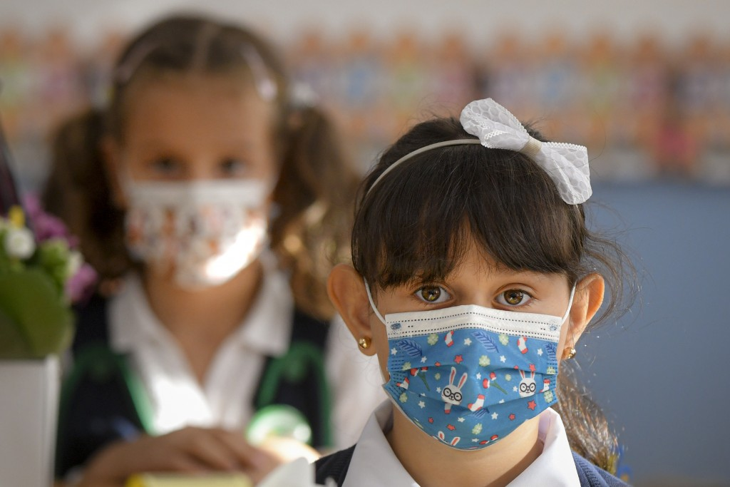 A girl wearing a face mask reacts during festivities marking the beginning of the school year at a school in Bucharest, Romania, Monday, Sept. 13, 202...