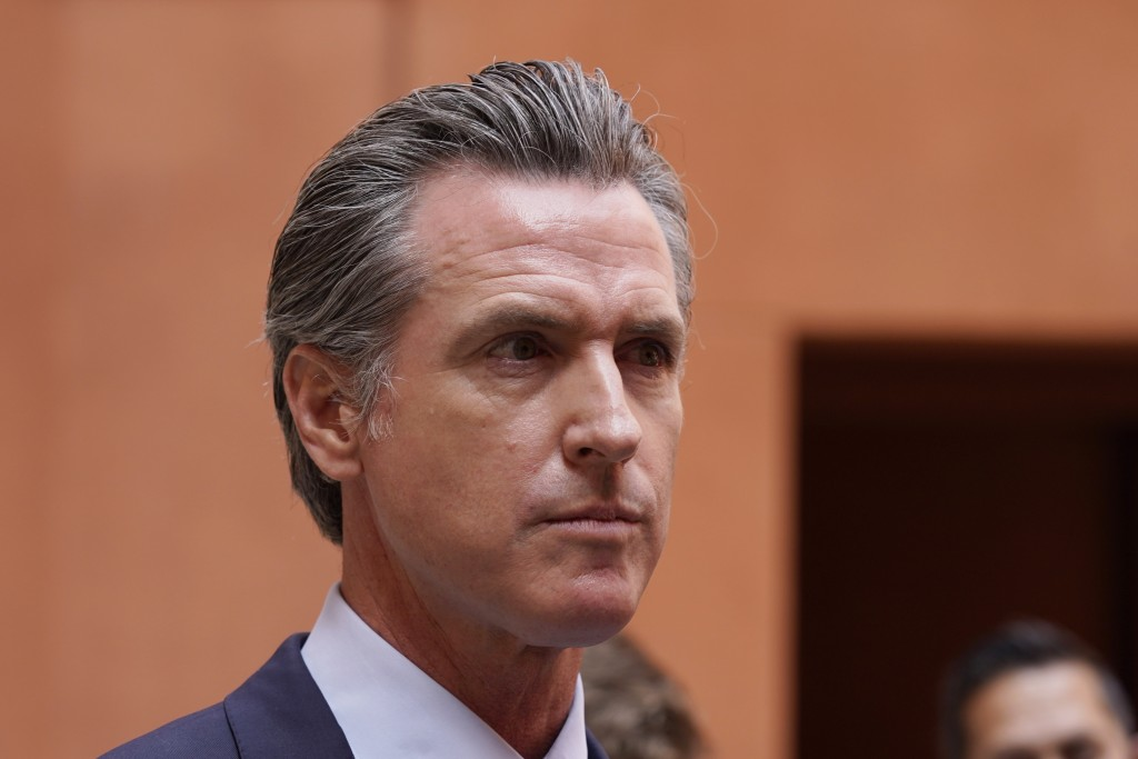 California Gov. Gavin Newsom listens to a question while meeting with reporters after casting his recall ballot at a voting center in Sacramento, Cali...