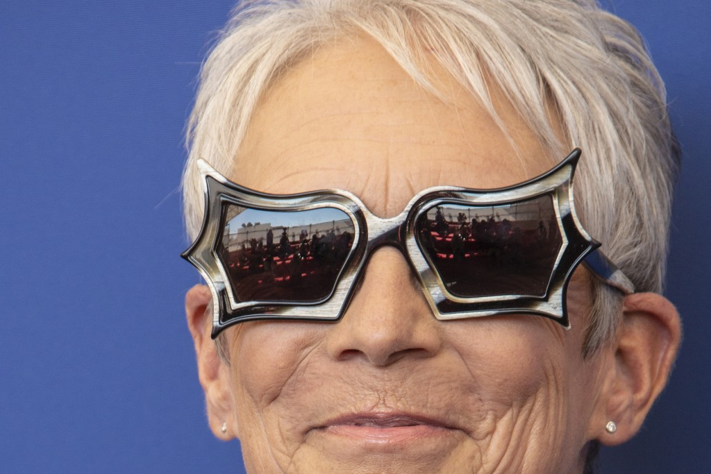 FILE - In this Sept, 8, 2021 file photo Jamie Lee Curtis poses for photographers, reflected in glasses, at the photo call for the film 'Halloween Kill...