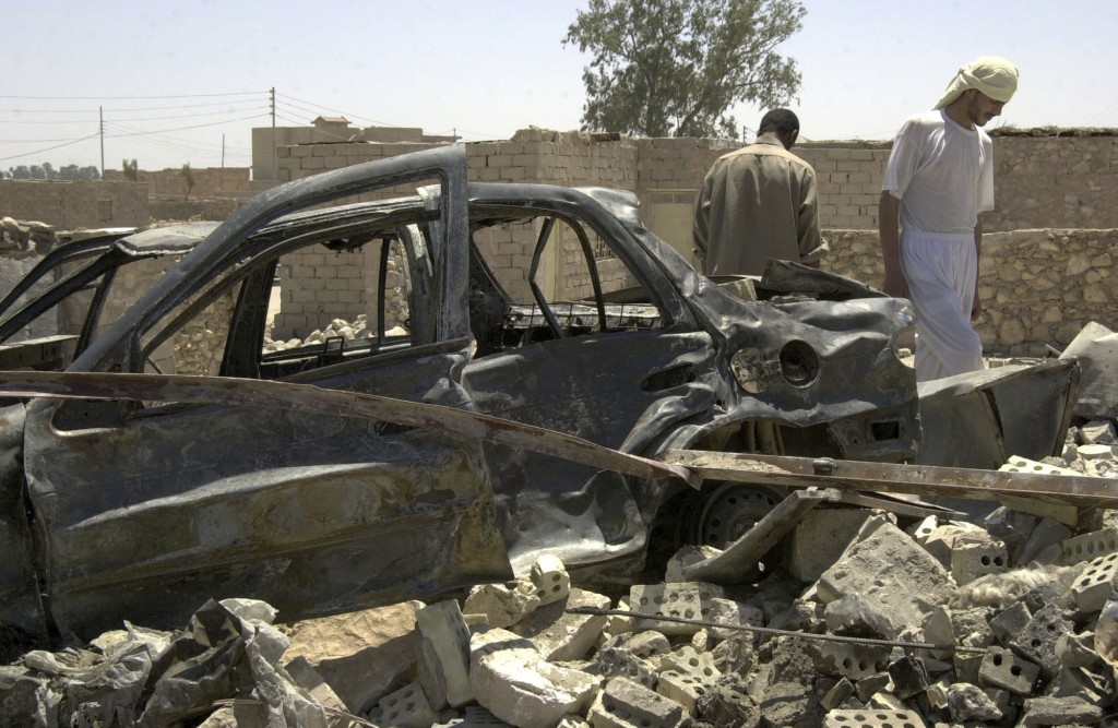 FILE- In this June 19, 2004, file photo, residents of a Fallujah, Iraq neighborhood walk through the wreckage of their homes which were destroyed in a...