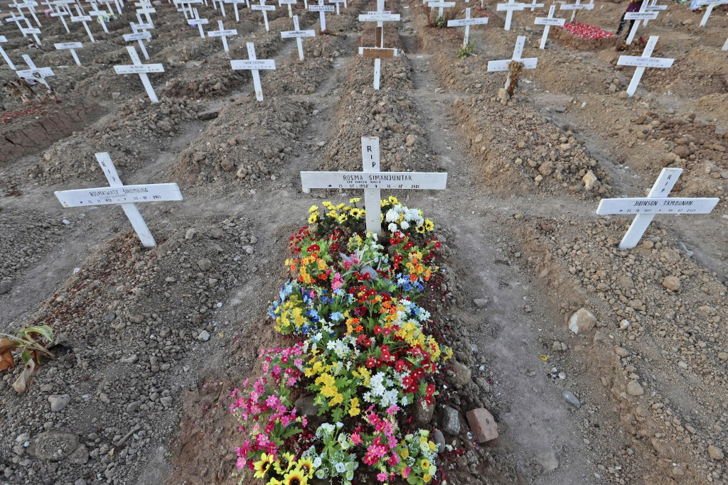 Flowers adorn a grave at Rorotan Cemetery in Jakarta, Indonesia, Wednesday, Sept. 1, 2021. In the graveyard on Jakarta's outskirts, portraits of the d...