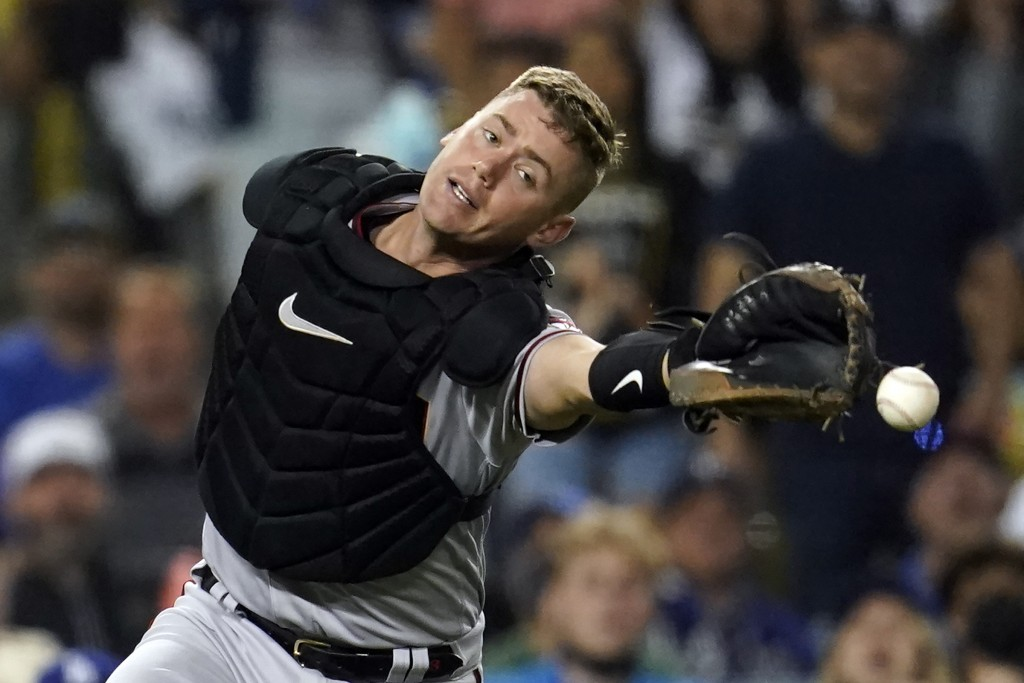 Arizona Diamondbacks catcher Carson Kelly reaches but cannot catch a foul ball from Los Angeles Dodgers' Cody Bellinger during the seventh inning of a...