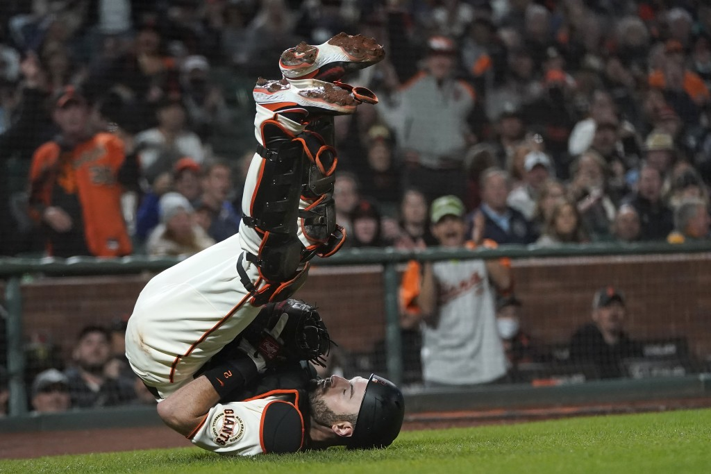 San Francisco Giants catcher Curt Casali falls backward after catching an out in foul territory hit by San Diego Padres' Fernando Tatis Jr. during the...