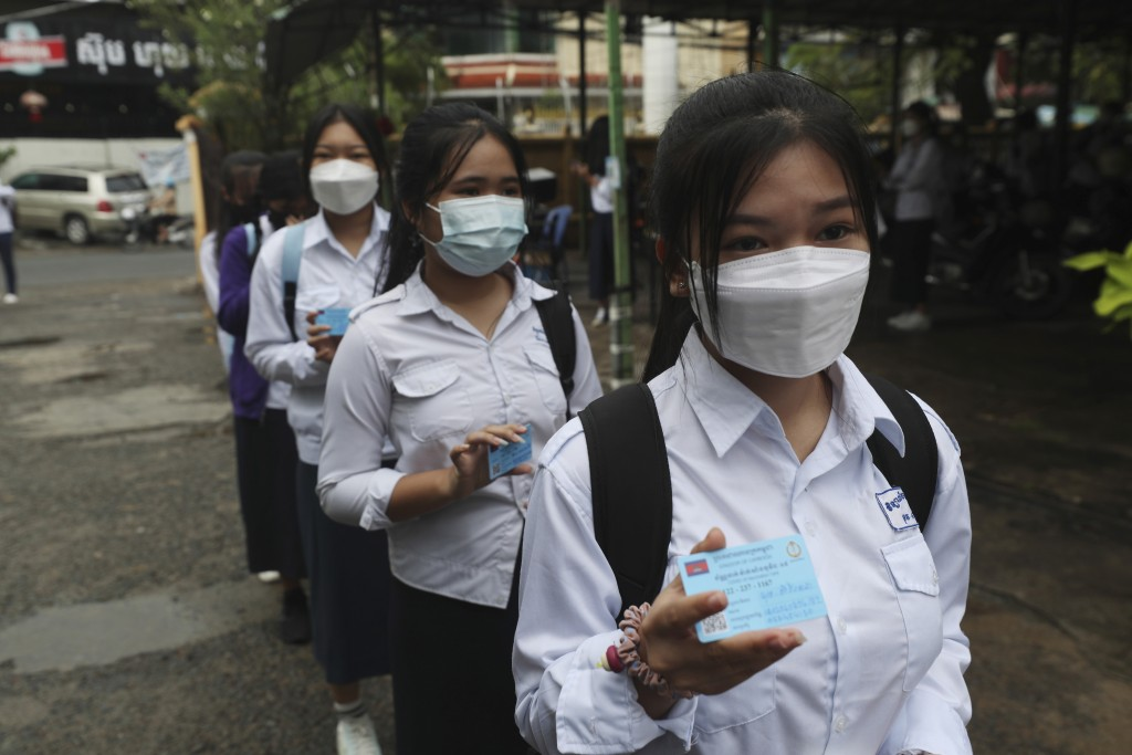Students show off the COVID-19 vaccination pass before their morning classes at the Preah Sisowath high school, in Phnom Penh, Cambodia, Wednesday, Se...