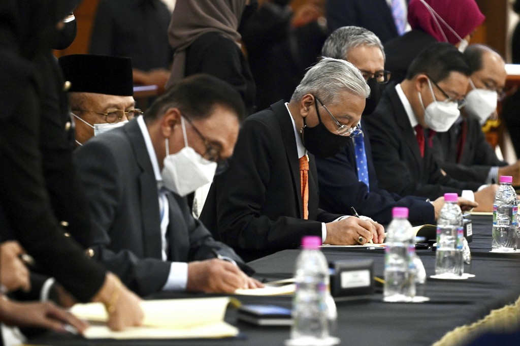 In this photo released by Malaysia's Department of Information, Malaysian Prime Minister Ismail Sabri Yaakob, center, and opposition leader Anwar Ibra...