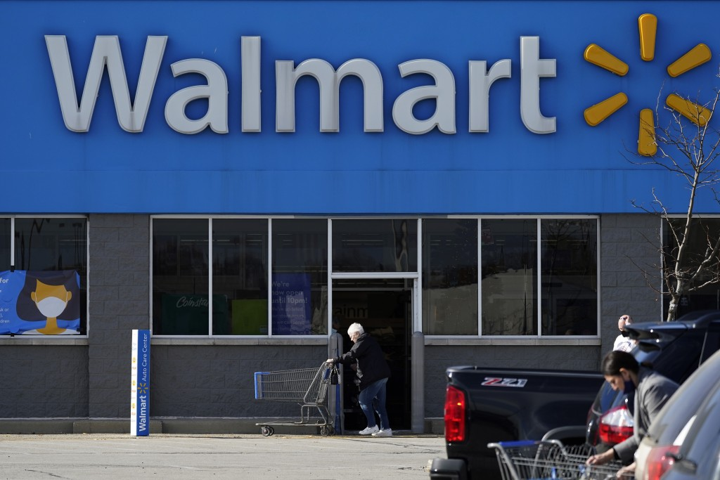 FILE - In this Nov. 5, 2020 file photo, a woman pushes a shopping cart to enter a Walmart in Rolling Meadows, Ill.    Walmart has denied any partnersh...