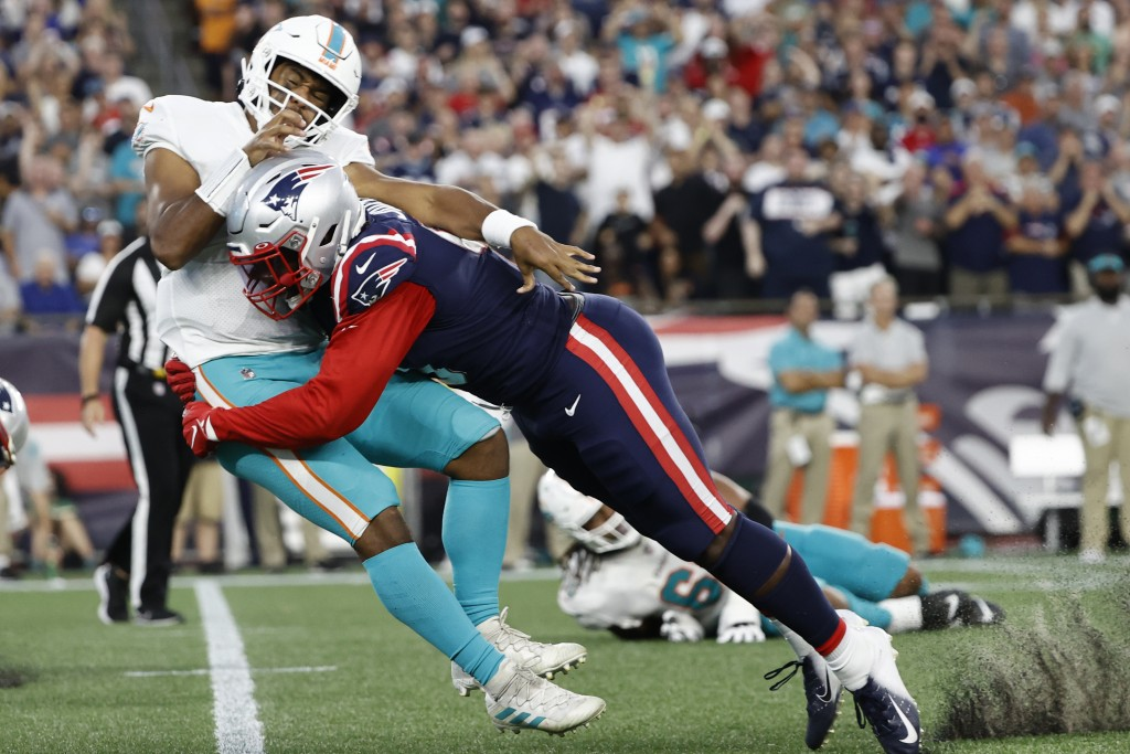 New England Patriots outside linebacker Matt Judon (9) tackles Miami Dolphins quarterback Tua Tagovailoa (1) during the second half of an NFL football...