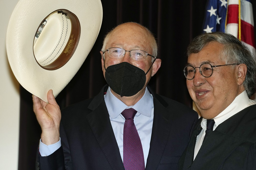 Ken Salazar, left, waves his hat before being sworn in as the United States ambassador to Mexico by Carlos F. Lucero, senior judge of the U.S. Court o...