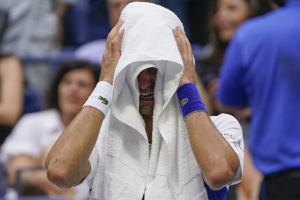 Novak Djokovic, of Serbia, cries as he sits on his bench during a changeover in the third set of the men's singles final against Daniil Medvedev, of R...