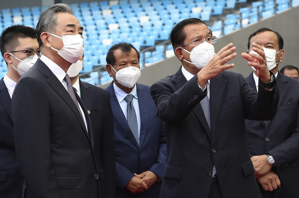 Chinese Foreign Minister Wang Yi, front left, listens to Cambodia's Prime Minister Hun Sen, front right, during a tour to the Morodok Techo National S...