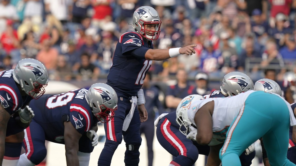 New England Patriots rookie quarterback Mac Jones (10) points on the line of scrimmage during the first half of an NFL football game against the Miami...